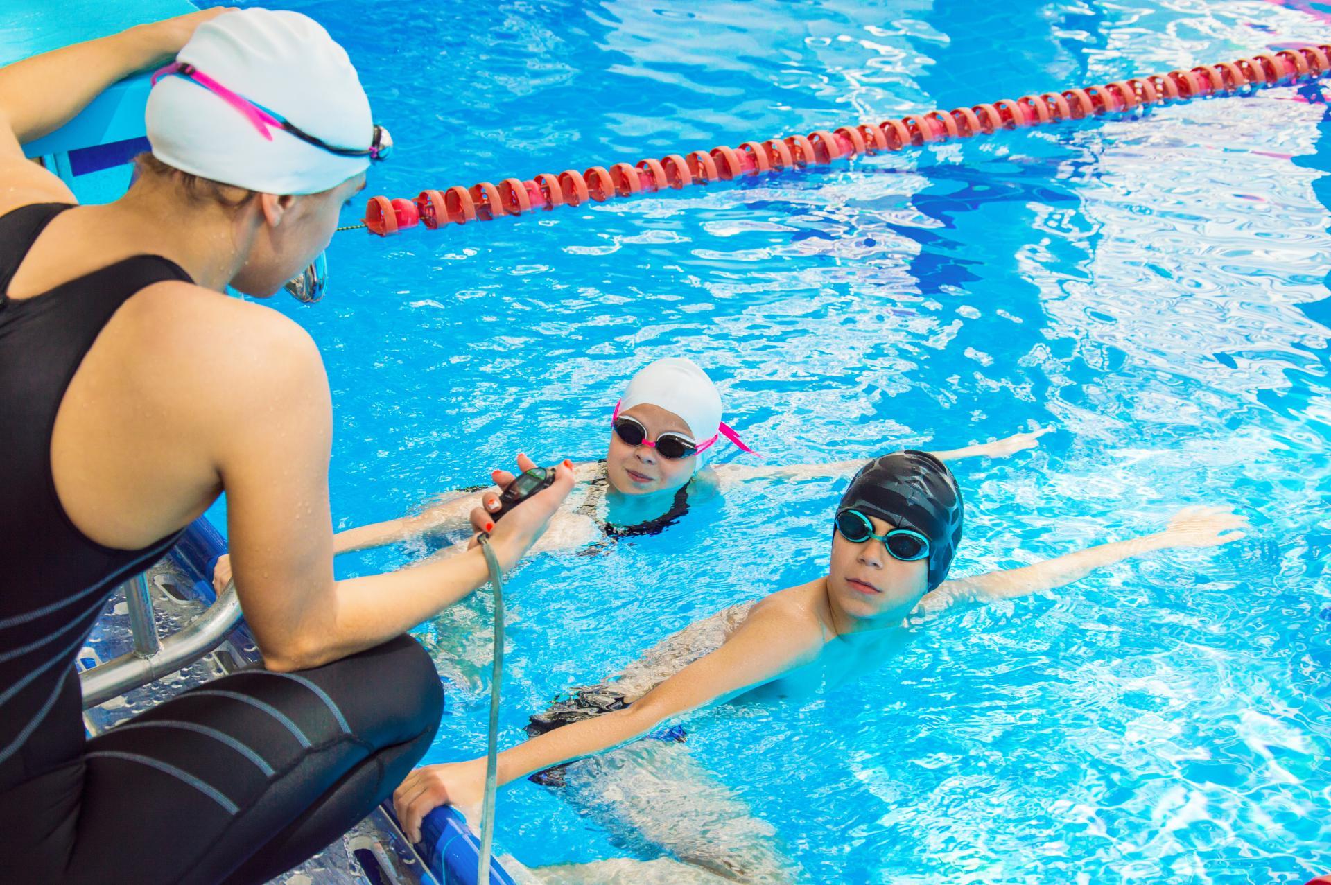 Deux enfants dans une piscine s'entraînent, leur entraîneur les chronomètre